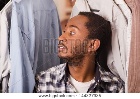 Headshot young man smiling to camera, sitting down with shirts hanging around his head, fashion concept.