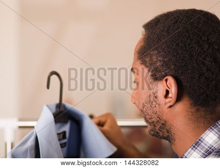 Headshot young man from behind, standing in front of clothing rack looking at blue shirt, fashion concept.