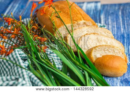 Fresh bread and flowers on blue wooden background and green fabric