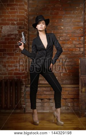 Noir Film Style Woman In A Black Suit With Gun