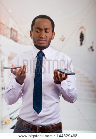 Handsome man wearing shirt and tie holding up two mobile phones with stressed facial expression.