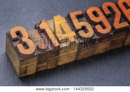 numerical representation of the pi number - vintage letterpress wood type against a slate stone
