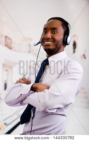 Handsome man wearing headphones with microphone, white striped shirt and tie, interacting confident, business concept.