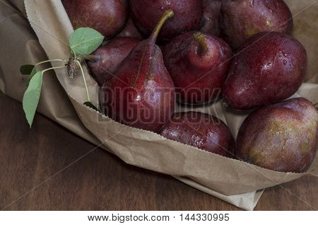 fresh red pears in a paper bag on the table