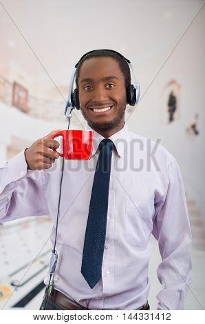 Handsome man wearing headphones with microphone, white striped shirt and tie, holding coffee mug smiling to camera, business concept.