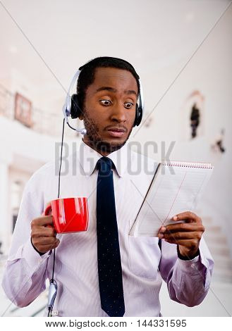 Handsome man wearing headphones with microphone, white striped shirt and tie, holding coffee mug, surprised facial expression, business concept.