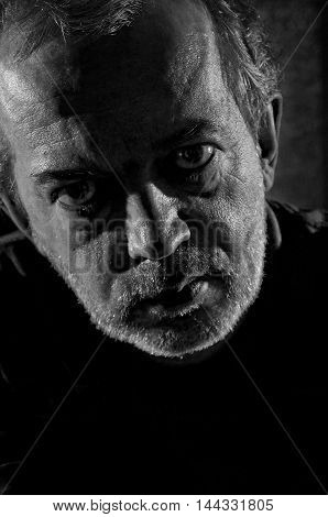 Black and white portrait of an old man who is angry.