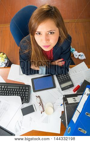 Young woman sitting by office desk with supplies spread out, interacting looking into camera as seen from above angle.