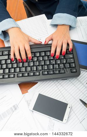 Closeup office womans fingers with red nailpolish writing on computer keyboard using both hands.
