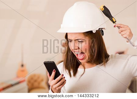 Young woman wearing construction helmet facing camera, looking at mobile screen, simulating smashing tool against her own head in frustration.