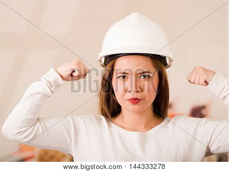 Young woman wearing construction helmet looking camera while lifting both fists up next to head.