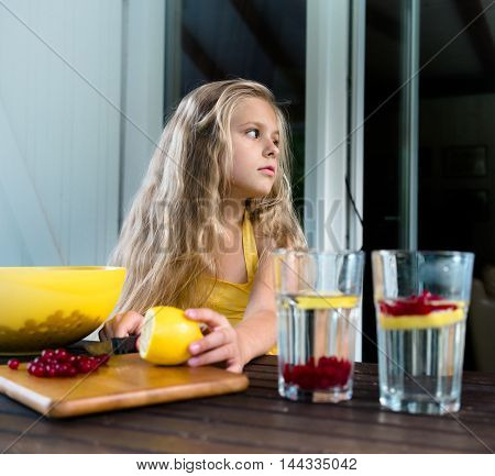 Pretty girl is preparing berry drink from a lemon and red currant
