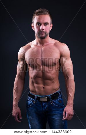 Portrait Of Young Muscular Man Standing Over Dark Background