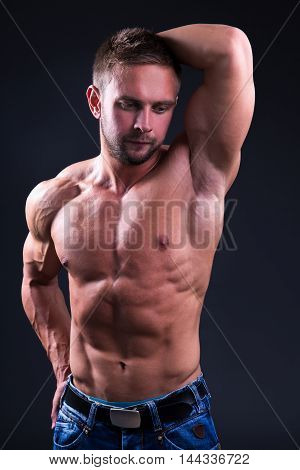 Young Muscular Man Posing Over Black Background