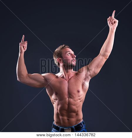 Young Muscular Man Pointing At Something Up Over Black Background