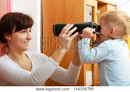 Happy childhood. Boy child kid son playing with camera taking photo his mother young woman. At home. Real.