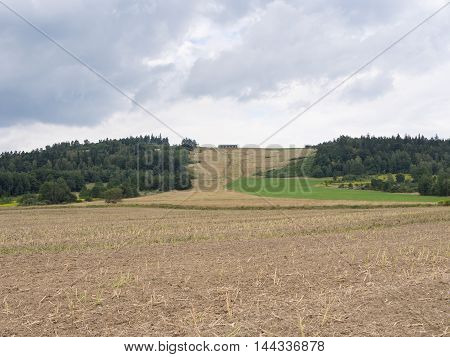 Field In Front Of A Woody Hill With A House