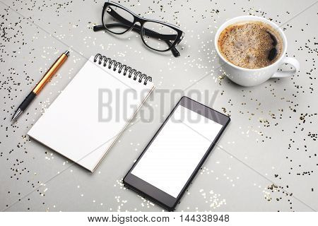 Notebook, coffee cup, smartphone and eye glasses are lying on grey festive background with little golden sparkles. Stuff for business women, top view. Place for text.
