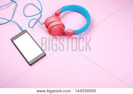 Pink and blue headphones and cellphone with white screen lying on pink background. With place for text on it.