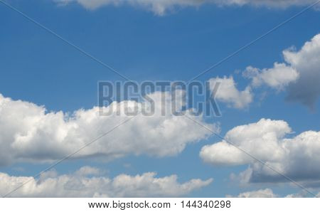Cumulus clouds in a bright, beautiful sunny sky.  Space for text.