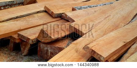 pile of rough cut teak lumber with bark and sawdust remaining on some pieces, temple construction site in southern Thailand