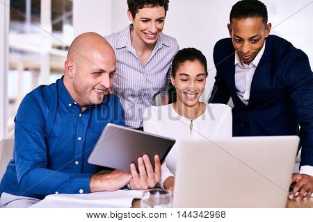 Horizontal image of four business people from diverse backgrounds, of multiethnic complexion unified by working together while looking at a laptop and electronic tablet.