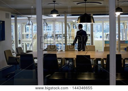 Successful business man with ambition standing alone in conference room while looking out the window thinking about several business stratergies that he might have to pursue soon.