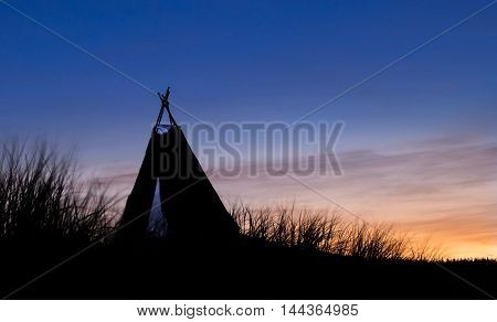 Tepee tent on a hill with dawn light behind it.