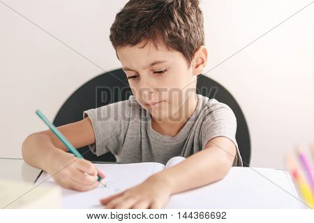Candid Portrait Of A Boy Doing His Homework And Studying At Home