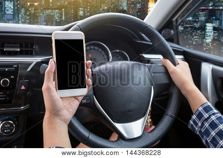 Young woman driver using touch screen smartphone and hand holding steering wheel in a car with night city background