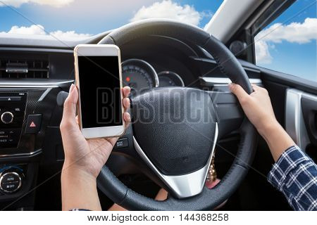 Young woman driver using touch screen smartphone and hand holding steering wheel in a car with blue sky and cloud background
