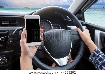 Young woman driver using touch screen smartphone and hand holding steering wheel in a car with sea beach and boat background
