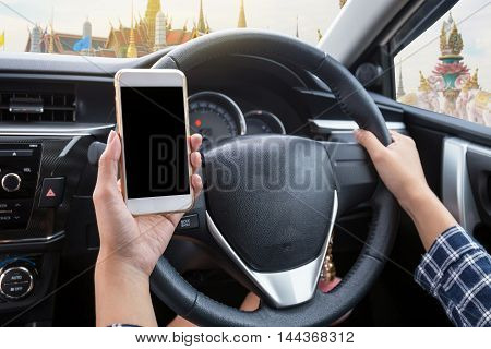 Young woman driver using touch screen smartphone and hand holding steering wheel in a car with Thai temple (Wat Phra Kaew or Temple of the Emerald Buddha) background