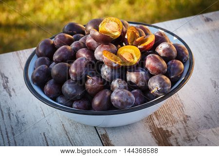 Heap Of Plums In Metal Bowl On Wooden Table In Garden On Sunny Day