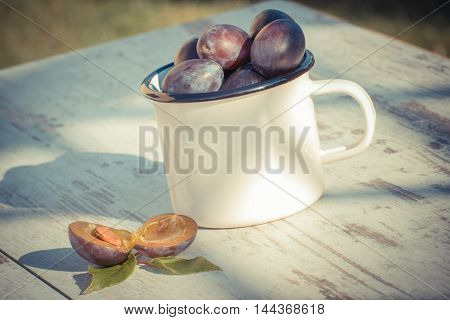 Vintage Photo, Heap Of Plums In Metallic Mug On Wooden Table In Garden On Sunny Day