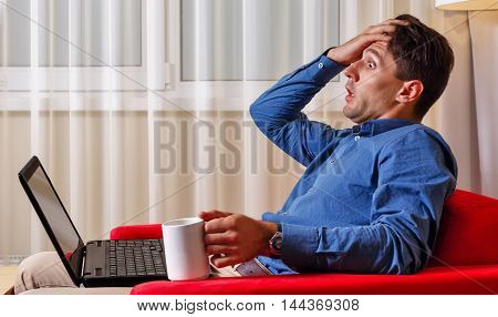 Man works for laptop. Businessman holding a cup of coffee and grabs his head. Bad news. Hard work.