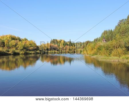 Autumn Russian landscape with old Church by the lake in Vyatka region.