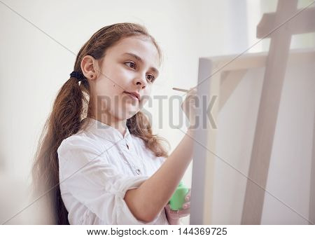Long-haired girl artist about canvas with brushes