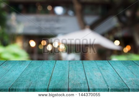 Perspective blue wooden table top with cafe blurred abstract background