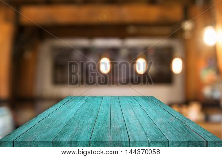 Perspective blue wooden table top with coffee shop blurred abstract background