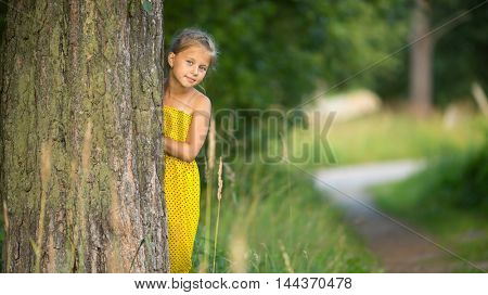 Little girl peeking from behind the tree.