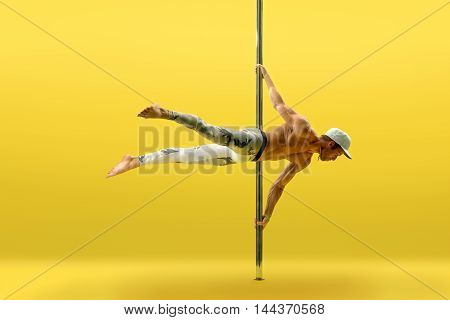 Studio image of acrobat exercising on pylon