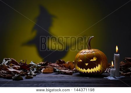 Pumpkin for Halloween, lamp of the pumpkin, witch silhouette, antique wood, celebrating halloween, smiley on a pumpkin, paraffin candles, burning candles, autumn dry leaves