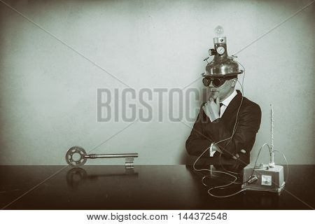 Vintage businessman sitting at office desk with key