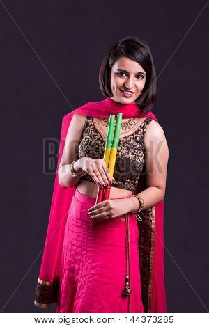 Indian beautiful young girl playing garba or ras garbha with garba sticks on Indian Festival Navratri, isolated on black background
