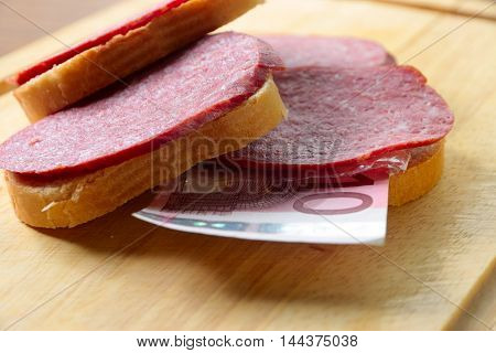 sandwich with sausage and euro on a wooden plate