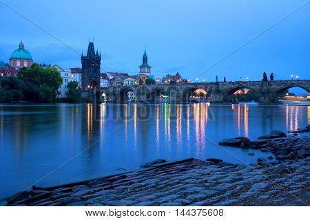 Blue hour view on Prague Charles Bridge. Scenic picture of Vltava river and bridge towers. Typical old bricks on the waterfront.