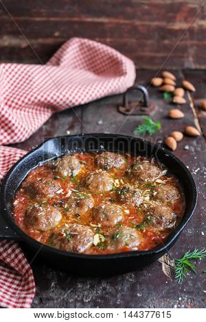 Moroccan meatballs with tomato sauce, spices, almond nuts and fresh dill in a pan on a wooden table, selective focus