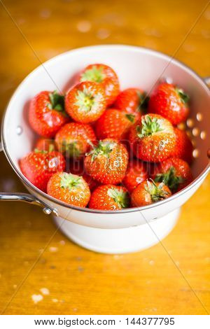 Fresh organic strawberry in a white colander on a wooden table, selective focus
