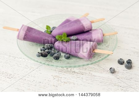 Blueberry popsicle with berries on wooden background.
